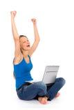 Muchacha con la computadora portátil que levanta sus brazos en alegría Imagenes de archivo