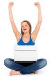 Muchacha con la computadora portátil que levanta sus brazos en alegría Fotos de archivo libres de regalías