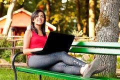 Muchacha con la computadora portátil que pone en banco Foto de archivo libre de regalías