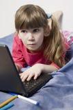 Muchacha con la computadora portátil que practica surf la red Fotografía de archivo