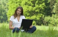 Muchacha con la computadora portátil que se relaja en la hierba Foto de archivo