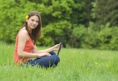 Muchacha con la computadora portátil que se relaja en la hierba Imagen de archivo libre de regalías
