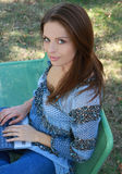 Muchacha con la computadora portátil que se relaja en la hierba Fotografía de archivo libre de regalías