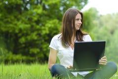 Muchacha con la computadora portátil que se relaja en la hierba, 'comm libre Imagenes de archivo