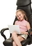 Muchacha con la computadora portátil que se sienta en una silla Fotografía de archivo