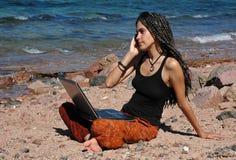 Muchacha con la computadora portátil y el teléfono celular en una playa Imágenes de archivo libres de regalías
