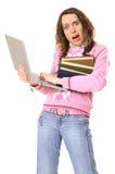 Muchacha con la computadora portátil y la pila de libros en pánico Imagen de archivo libre de regalías