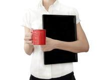 Muchacha con la computadora portátil y la taza de café roja en manos Foto de archivo libre de regalías