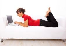 Muchacha con la computadora portátil en el sofá Fotografía de archivo