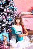Muchacha con la decoración y el árbol de la Navidad Foto de archivo libre de regalías