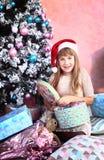 Muchacha con la decoración y el árbol de la Navidad Fotos de archivo