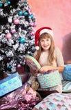 Muchacha con la decoración y el árbol de la Navidad Imagen de archivo
