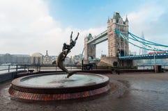 Muchacha con la estatua del delfín y el puente de la torre Fotografía de archivo