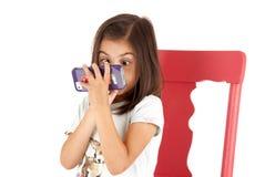 Muchacha con la expresión con los ojos abiertos que juega al juego en pho Fotos de archivo