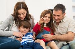 Muchacha con la familia que muestra llave de la casa Imagenes de archivo