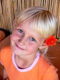 muchacha con la flor detrás del oído imagen de archivo