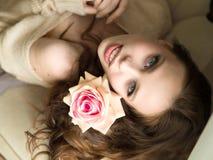 Muchacha con la flor Mujer joven hermosa que celebra la rosa y la sonrisa del rojo Imágenes de archivo libres de regalías