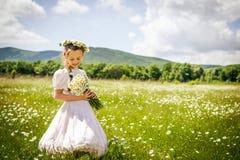 Muchacha con la guirnalda de la manzanilla en campo del verano Foto de archivo