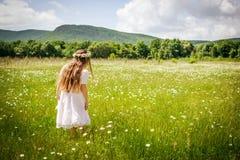 Muchacha con la guirnalda de la manzanilla en el campo Fotos de archivo