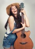 Muchacha con la guitarra acústica Imagen de archivo libre de regalías