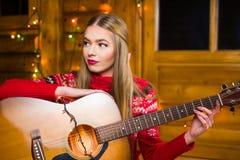Muchacha con la guitarra acústica en el ambiente festivo Imagen de archivo