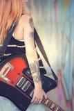 Muchacha con la guitarra eléctrica cerca de la pared de la pintada Primer Foto de archivo