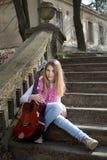 Muchacha con la guitarra que se sienta en las escaleras al aire libre en Sunny Day Foto de archivo libre de regalías