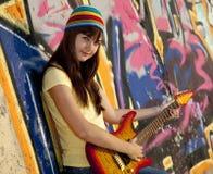 Muchacha con la guitarra y la pared de la pintada Imágenes de archivo libres de regalías
