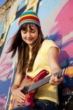 Muchacha con la guitarra y la pared de la pintada Imagen de archivo