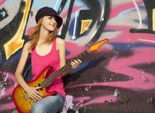 Muchacha con la guitarra y la pared de la pintada Fotos de archivo