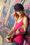 Muchacha con la guitarra y la pared de la pintada Imagenes de archivo