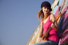 Muchacha con la guitarra y la pared de la pintada Fotos de archivo libres de regalías