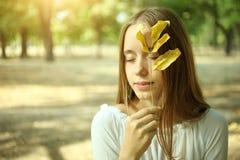 Muchacha con la hoja del otoño Imágenes de archivo libres de regalías