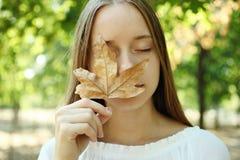 Muchacha con la hoja del otoño Imagen de archivo libre de regalías