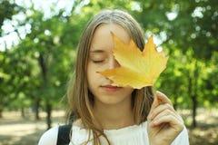 Muchacha con la hoja del otoño Fotografía de archivo libre de regalías
