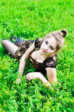 Muchacha con la lámina de la hierba en su boca Imagenes de archivo