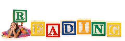 Muchacha con la lectura del bloque del alfabeto Imagen de archivo libre de regalías