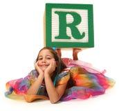 Muchacha con la letra de molde del alfabeto R Fotos de archivo