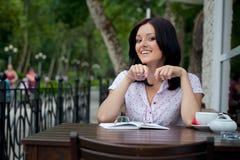 Muchacha con la libreta en café Fotografía de archivo libre de regalías