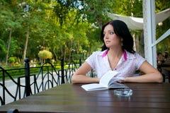 Muchacha con la libreta en café foto de archivo