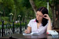 Muchacha con la libreta en café imagen de archivo libre de regalías