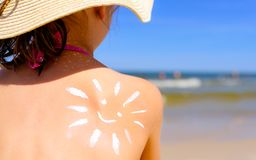 Muchacha con la loción del bronceado en la playa en la forma del sol fotos de archivo libres de regalías