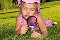 Muchacha con la lupa imagen de archivo