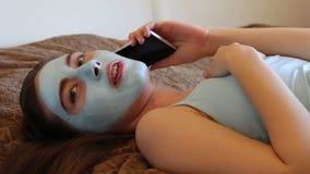 Muchacha con la máscara cosmética en su cara que habla en el smartphone metrajes