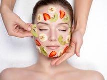 Muchacha con la máscara del facial de la fruta Foto de archivo libre de regalías