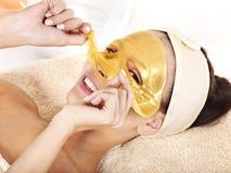 Muchacha con la máscara del facial del oro. imagenes de archivo