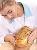 Muchacha con la máscara del facial del oro. fotografía de archivo