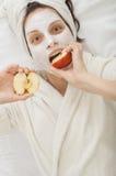 Muchacha con la máscara facial del krem que muerde una manzana Fotos de archivo libres de regalías