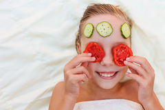 Muchacha con la máscara facial del pepino y de tomates Imagen de archivo