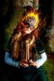 Muchacha con la máscara shamanic de la pluma y vestido histórico en los alrededores del arbolado que tocan la flauta ornamental d Imagen de archivo